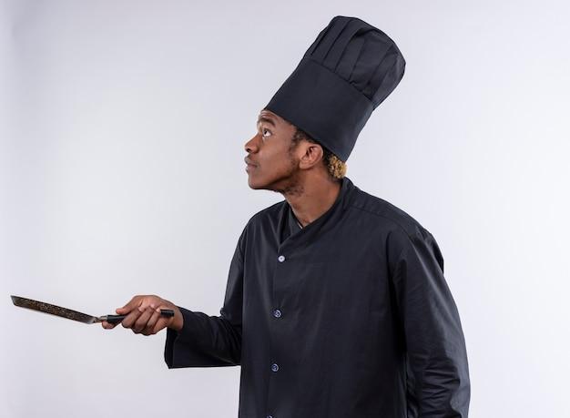 Jonge angstige afro-amerikaanse kok in uniform chef staat zijwaarts en houdt koekenpan geïsoleerd op een witte achtergrond met kopie ruimte