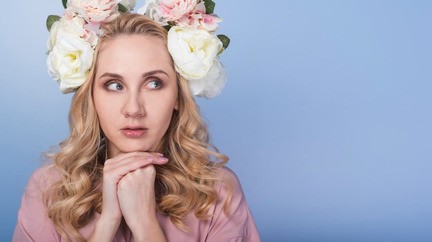 Jonge angstige blonde dame met mooie bloemkroon
