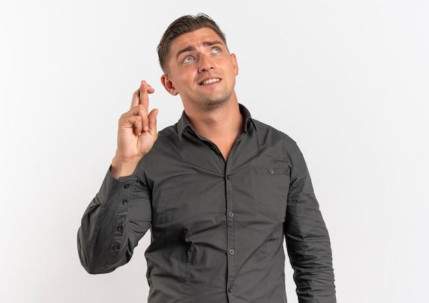 Jonge angstige blonde knappe man staat met gekruiste vingers opzoeken geïsoleerd op een witte achtergrond met kopie ruimte