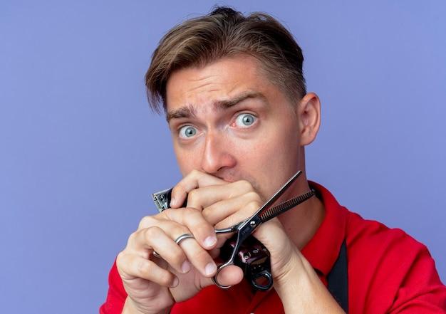 Jonge angstige blonde mannelijke kapper in uniform houdt schaar en tondeuse geïsoleerd op violette ruimte met kopie ruimte