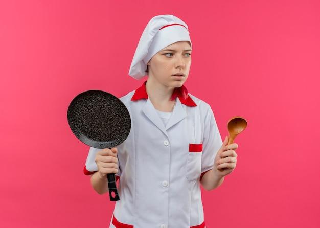 Jonge angstige blonde vrouwelijke chef-kok in uniform chef houdt koekenpan en houten lepel op zoek naar de kant geïsoleerd op roze muur