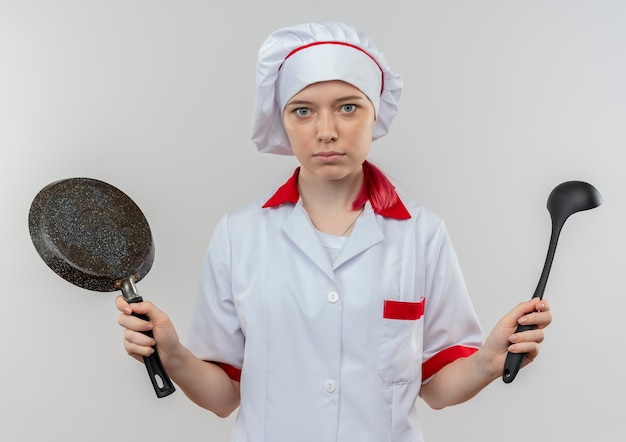 Jonge angstige blonde vrouwelijke chef-kok in uniform chef houdt koekenpan en pollepel geïsoleerd op een witte muur