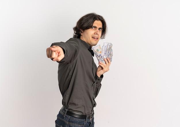 Jonge angstige knappe blanke man staat zijwaarts geld vasthouden en wijst naar camera geïsoleerd op een witte achtergrond met kopie ruimte