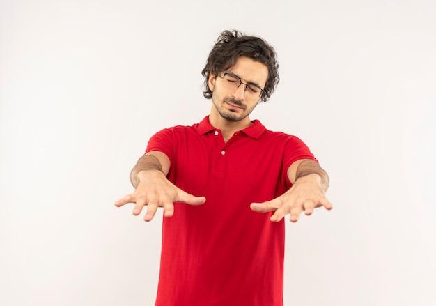 Jonge angstige man in rood shirt met optische bril houdt handen uit met gesloten ogen geïsoleerd op een witte muur