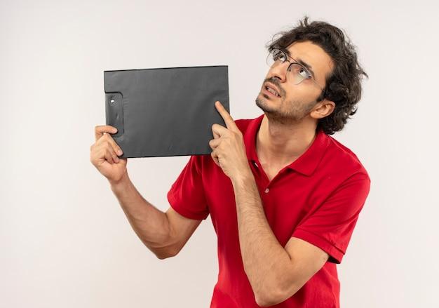 Jonge angstige man in rood shirt met optische bril houdt klembord en kijkt omhoog geïsoleerd op een witte muur
