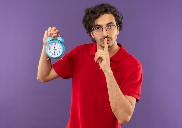 Jonge angstige man in rood shirt met optische bril houdt klok en gebaren stilte teken geïsoleerd op violette muur