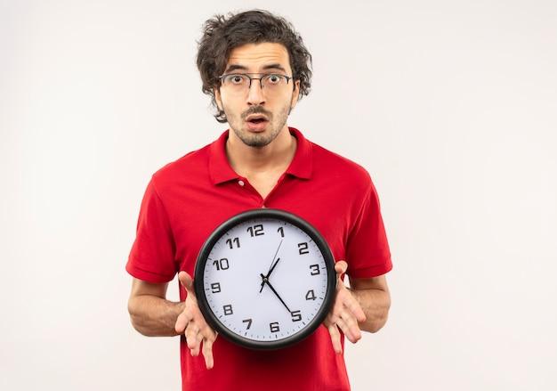 Jonge angstige man in rood shirt met optische bril houdt klok en kijkt geïsoleerd op een witte muur