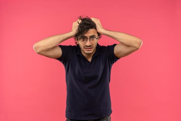 Jonge angstige man in zwart shirt met optische bril houdt hoofd met handen en kijkt geïsoleerd op roze muur