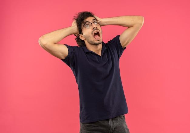 Jonge angstige man in zwart shirt met optische bril houdt hoofd vast en kijkt omhoog geïsoleerd op roze muur