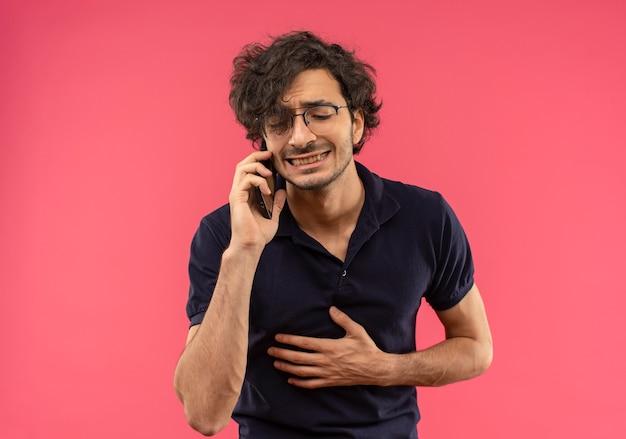 Jonge angstige man in zwart shirt met optische bril praat aan de telefoon en houdt buik geïsoleerd op roze muur