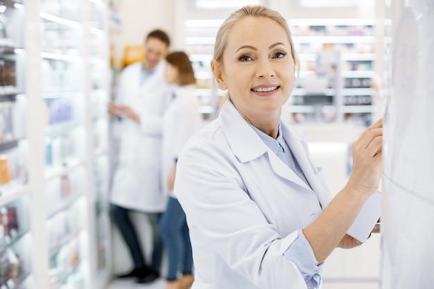 Jonge apotheker die drugs in een winkel controleert