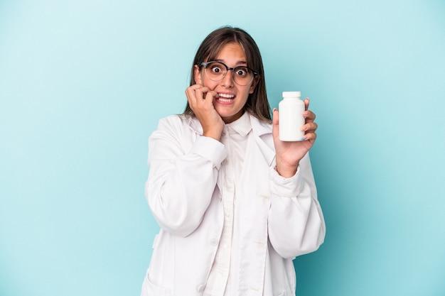 Jonge apotheker vrouw met pillen geïsoleerd op blauwe achtergrond vingernagels bijten, nerveus en erg angstig.