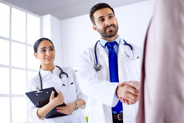 Jonge arabische arts schudt handen met een patiënt in het ziekenhuis