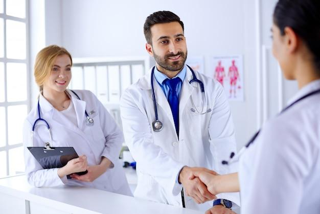 Jonge arabische arts schudt handen met een verpleegster in het ziekenhuis. tegen de achtergrond van het menselijk lichaam