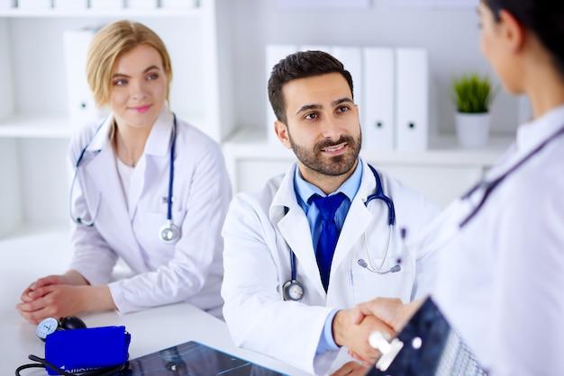 Jonge arabische arts schudt handen met verpleegkundigen in het ziekenhuis. groep jonge artsen op kantoor