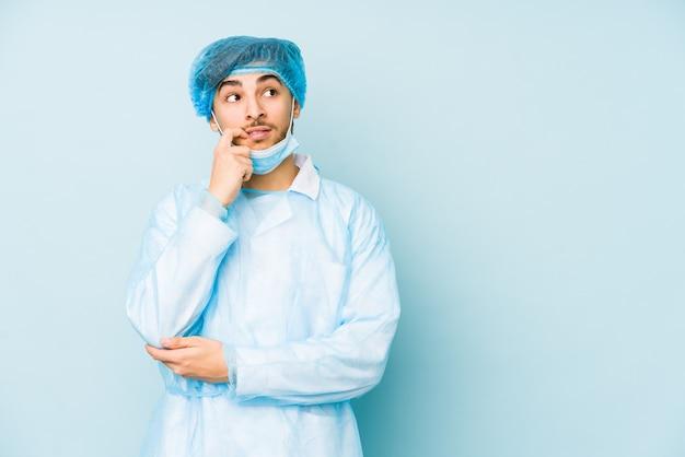 Jonge arabische chirurgenmens die tegen bij het blauwe ontspannen denken over iets wordt geïsoleerd dat een exemplaarruimte bekijkt.