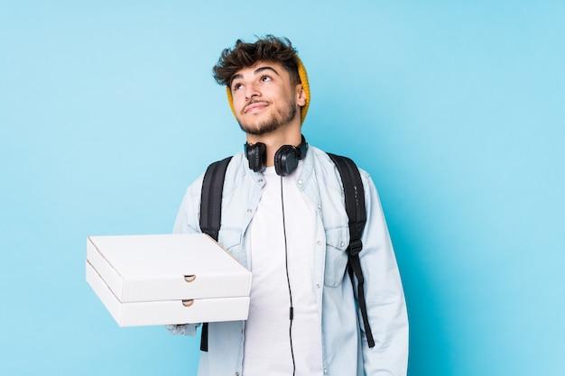 Jonge arabische de holdingspizza's van de studentenmens geïsoleerde het dromen van het bereiken van doelstellingen en doeleinden