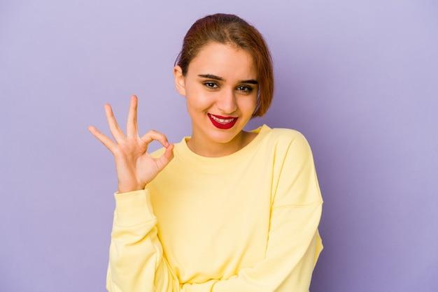 Jonge arabische gemengd ras vrouw knipoogt een oog en houdt een goed gebaar met de hand.