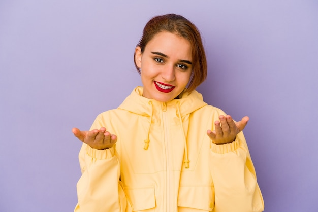 Jonge arabische gemengde rasvrouw die een welkome uitdrukking toont.