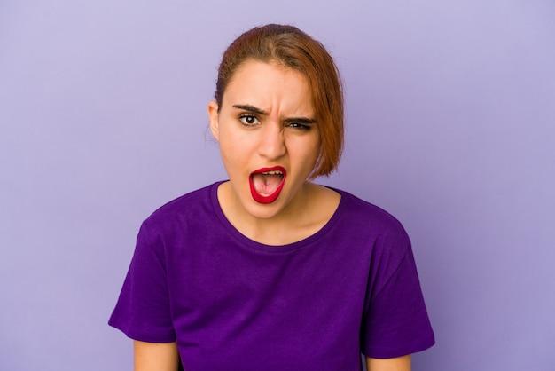 Jonge arabische gemengde rasvrouw die zeer boos, gefrustreerd woedeconcept schreeuwt.