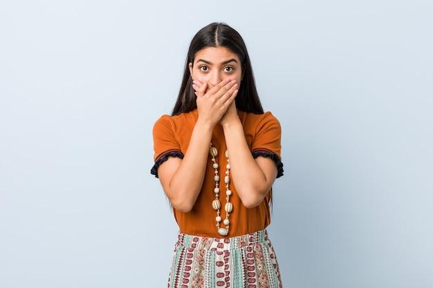 Jonge arabische geschokte vrouw het behandelen van mond met handen.