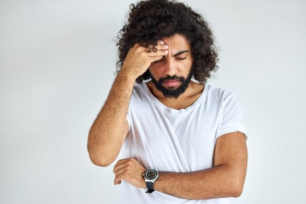 Jonge arabische indiase man met lang haar heeft hoofdpijn