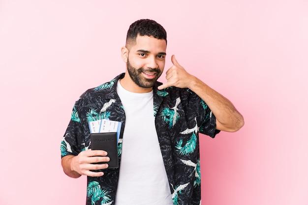 Jonge arabische koele mens die instapkaarten houden geïsoleerd tonend een mobiel telefoongesprekgebaar met vingers.