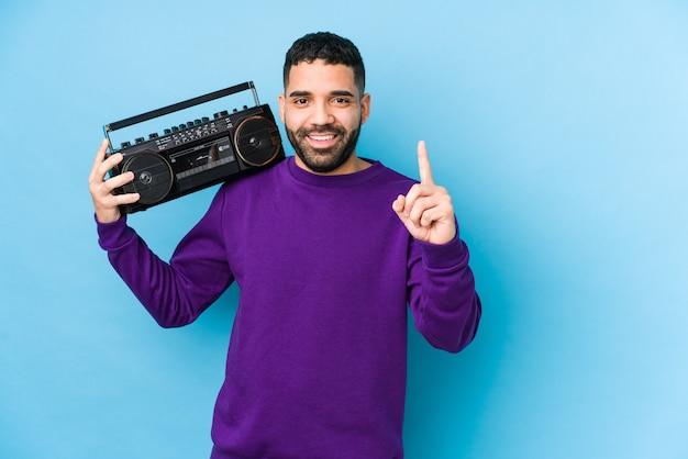 Jonge arabische man die een geïsoleerde radiocassette houdt jonge arabische man het luisteren muziek die nummer één met vinger toont.