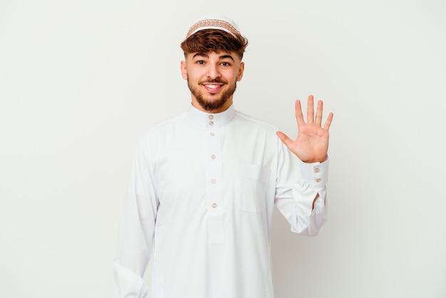Jonge arabische man die het typische arabische kostuum draagt dat op wit wordt geïsoleerd, vrolijk glimlachend toont nummer vijf met vingers.