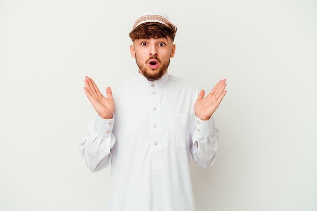 Jonge arabische man die het typische arabische kostuum draagt dat op witte achtergrond wordt geïsoleerd verrast en geschokt.
