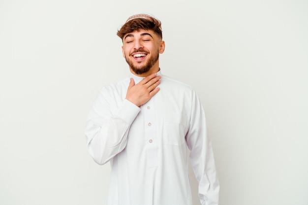 Jonge arabische man die het typische arabische kostuum draagt, lacht hardop terwijl hij de hand op de borst houdt.