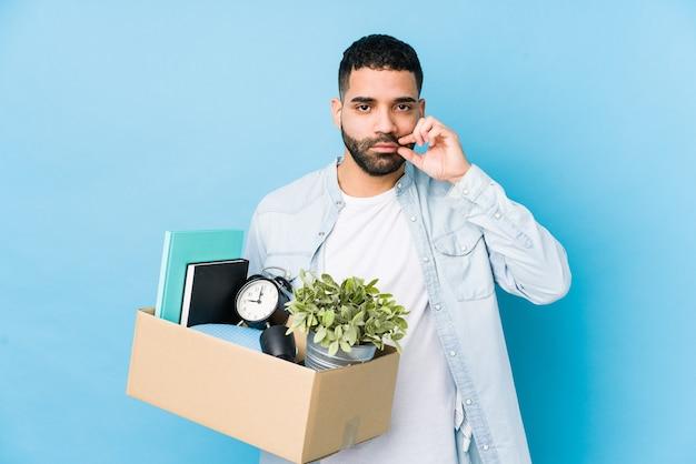 Jonge arabische man die naar een nieuw huis verhuist dat met vingers op lippen wordt geïsoleerd die een geheim bewaren.
