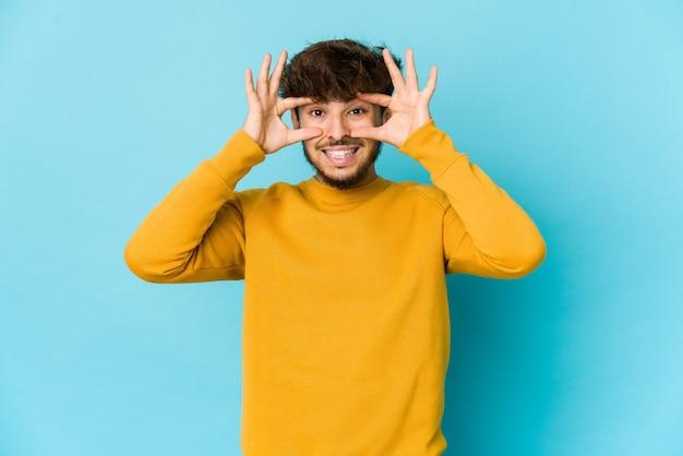 Jonge arabische man die op blauwe achtergrond ogen openhouden om een succeskans te vinden.