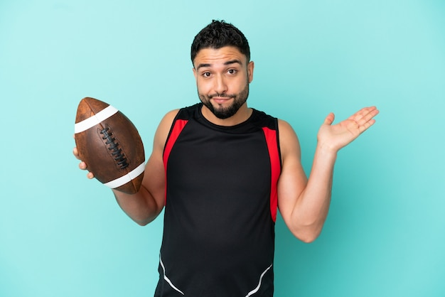 Jonge arabische man die rugby speelt geïsoleerd op een blauwe achtergrond met twijfels terwijl hij zijn handen opsteekt