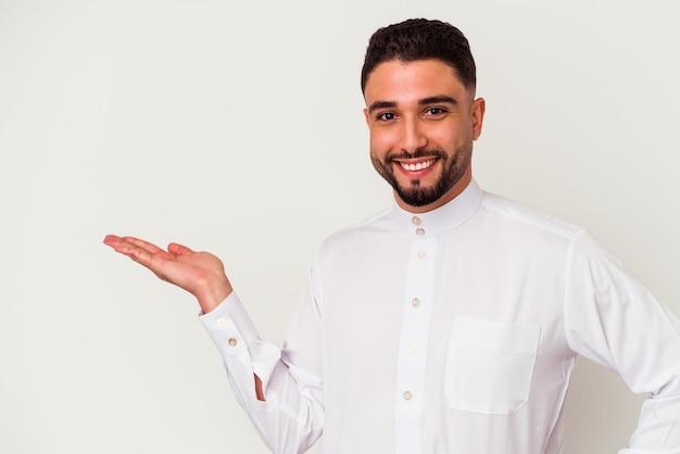 Jonge arabische man die typische arabische kleding draagt die op witte achtergrond wordt geïsoleerd die een exemplaarruimte op een palm toont en een andere hand op taille houdt.