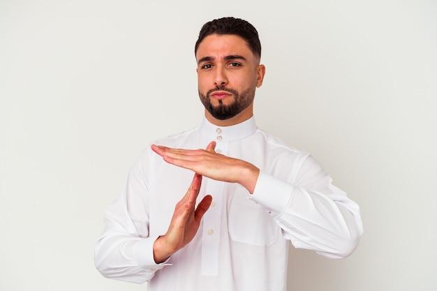Jonge arabische man die typische arabische kleding draagt die op witte achtergrond wordt geïsoleerd die een time-outgebaar toont.