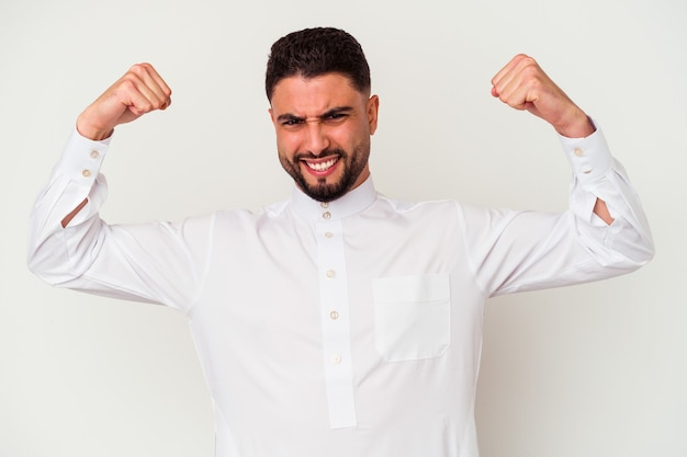 Jonge arabische man die typische arabische kleding draagt die op witte achtergrond wordt geïsoleerd die krachtgebaar met wapens toont, symbool van vrouwelijke macht
