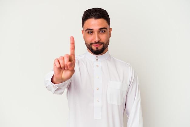 Jonge arabische man die typische arabische kleding draagt die op witte achtergrond wordt geïsoleerd die nummer één met vinger toont.