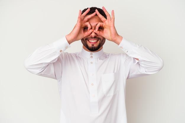 Jonge arabische man die typische arabische kleding draagt die op witte achtergrond wordt geïsoleerd die ok teken over ogen toont