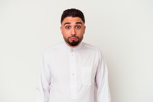 Jonge arabische man die typische arabische kleding draagt die op witte achtergrond wordt geïsoleerd, haalt zijn schouders op en opent verwarde ogen.