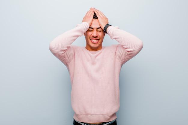 Jonge arabische man die zich gestrest en angstig, depressief en gefrustreerd voelt door hoofdpijn, beide handen opheft om tegen de grijze muur te gaan