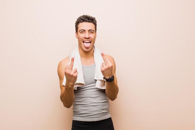 Jonge arabische man die zich provocerend, agressief en obsceen voelt, de middelvinger omdraait, met een rebelse houding. sport concept