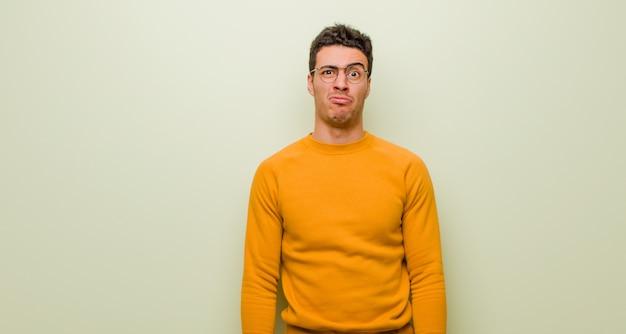 Jonge arabische man die zich verdrietig en gestrest voelt, van streek is vanwege een onaangename verrassing, met een negatieve, angstige blik tegen een vlakke muur