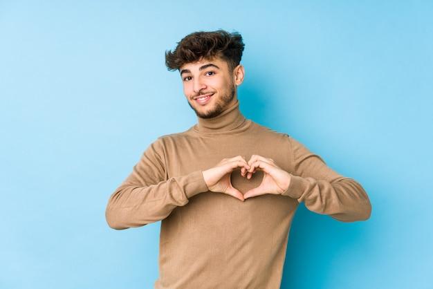 Jonge arabische man geïsoleerd glimlachend en een hartvorm met handen tonen.