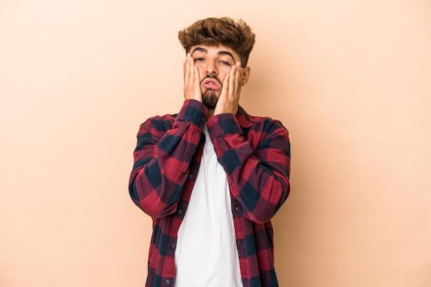 Jonge arabische man geïsoleerd op beige achtergrond jammerend en huilend troosteloos.