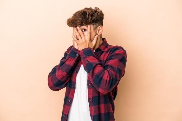Jonge arabische man geïsoleerd op beige achtergrond knipperen door vingers bang en nerveus.