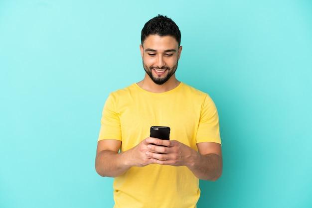 Jonge arabische man geïsoleerd op blauwe achtergrond die een bericht verzendt met de mobiel