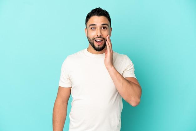 Jonge arabische man geïsoleerd op blauwe achtergrond met verrassing en geschokte gezichtsuitdrukking