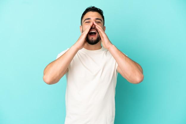 Jonge arabische man geïsoleerd op blauwe achtergrond schreeuwen en iets aankondigen