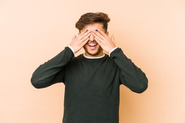 Jonge arabische man geïsoleerd op een beige muur bedekt ogen met handen, glimlacht breed wachtend op een verrassing.